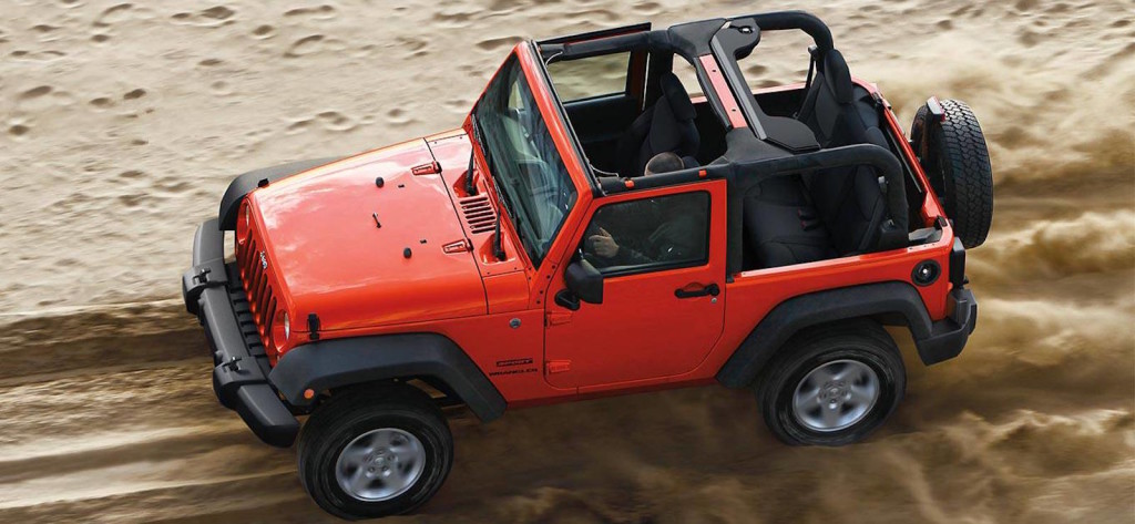 Red 2016 Jeep Wrangler is shown from above, driving on a sand trail in Colorado Springs, CO.