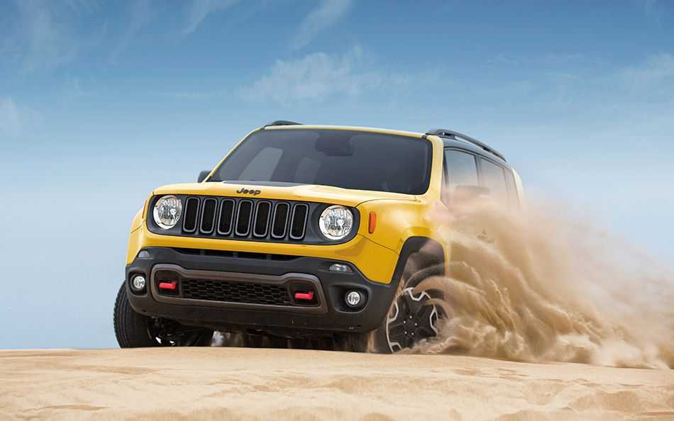 A yellow 2015 Jeep Renegade is kicking up sand in a dune.