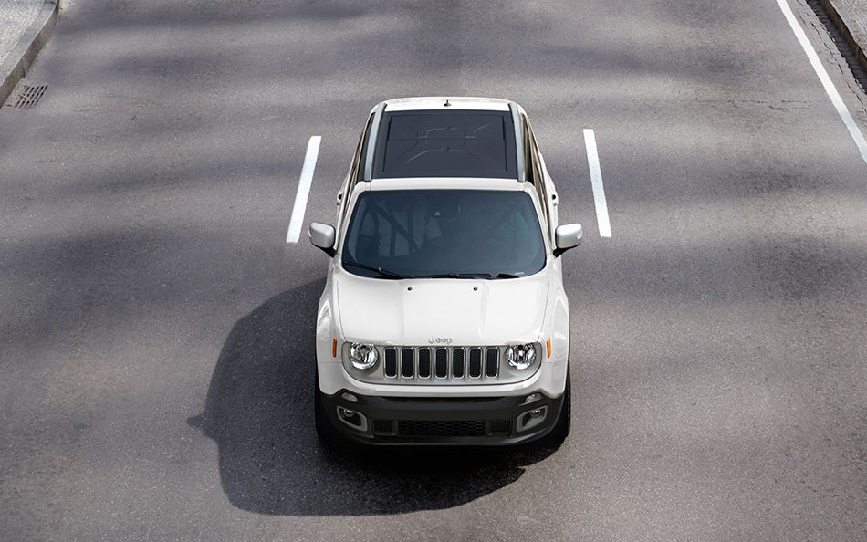 A white 2015 Jeep Renegade is driving on an empty road and is shown from above.
