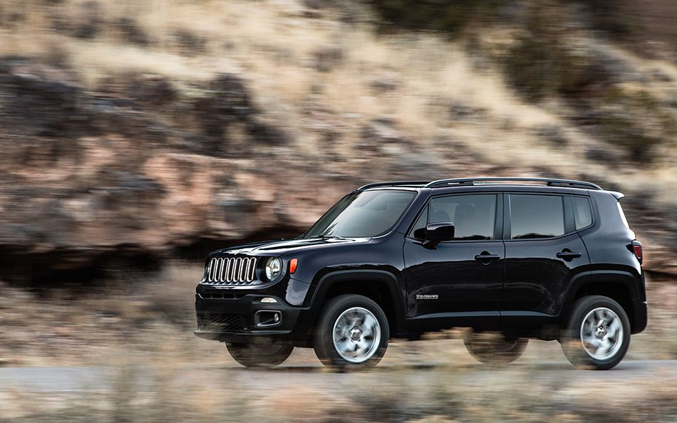 A black 2015 Jeep Renegade is driving on a desert road.