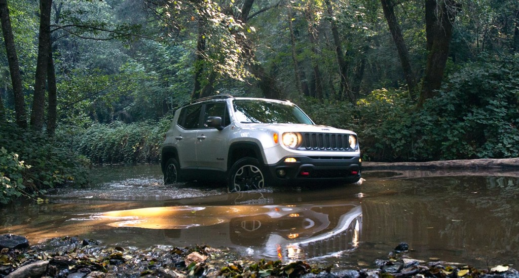 A silver 2015 Jeep Renegade is crossing a puddle on a woodland trail.
