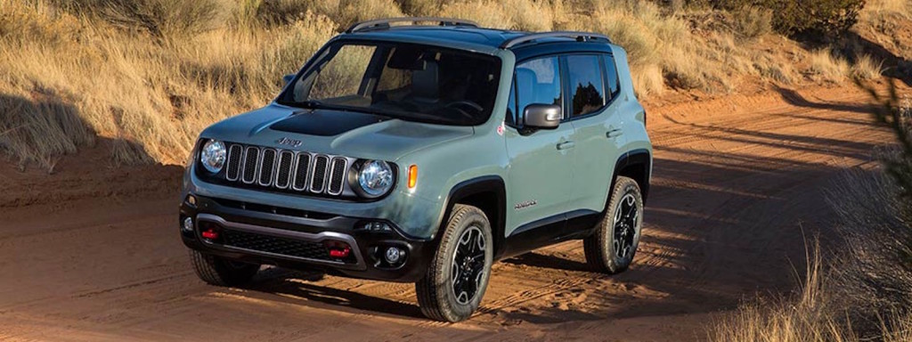 A blue/green 2016 Jeep Renegade is driving on a dirt road.