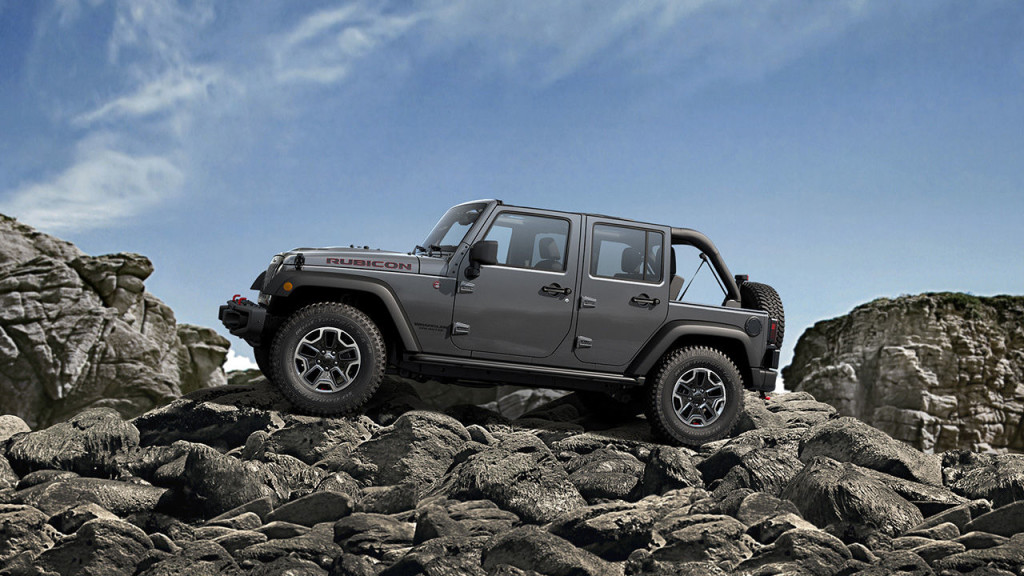 A gray 2016 Jeep Wrangler Unlimited Rubicon is driving over rocks against a blue sky.