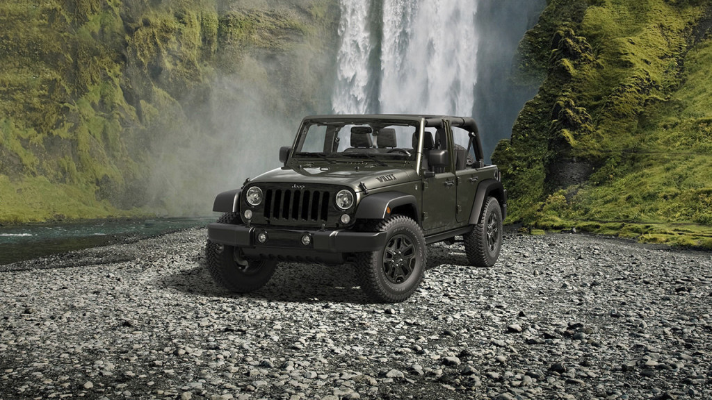 A green 2016 Jeep Wrangler Unlimited Willy's Wheeler is parked in front of a waterfall.