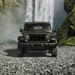 A green 2016 Jeep Wrangler Unlimited Willy's Wheeler is parked in front of a waterfall and shown from the front.