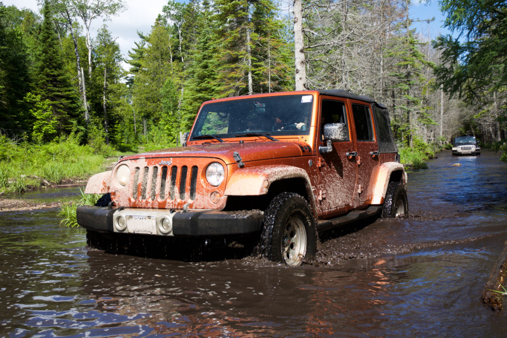 An orange Jeep Wrangler is driving through a woodland river.