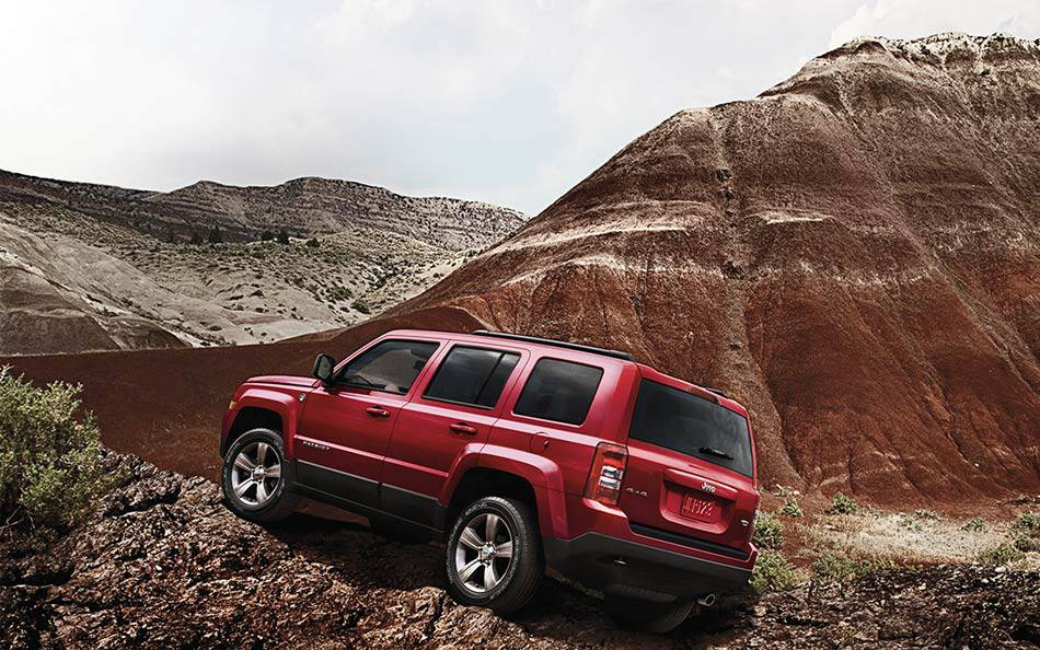 A red 2014 Jeep Patriot from a Jeep dealer in Colorado is climbing rocks in a desert.
