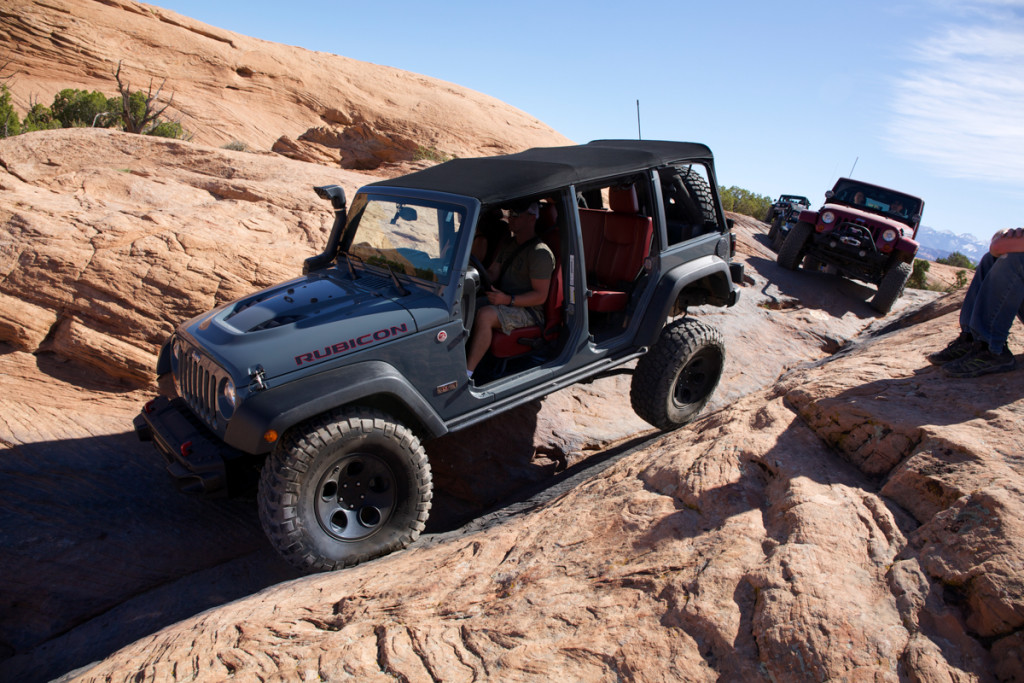 A gray 2015 Jeep Wrangler Unlimited Rubicon without doors is climbing over rocks on a trail.