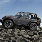 A gray 2016 Jeep Wrangler Rubicon with no roof is climbing over rocks in Colorado Springs, against a blue sky.