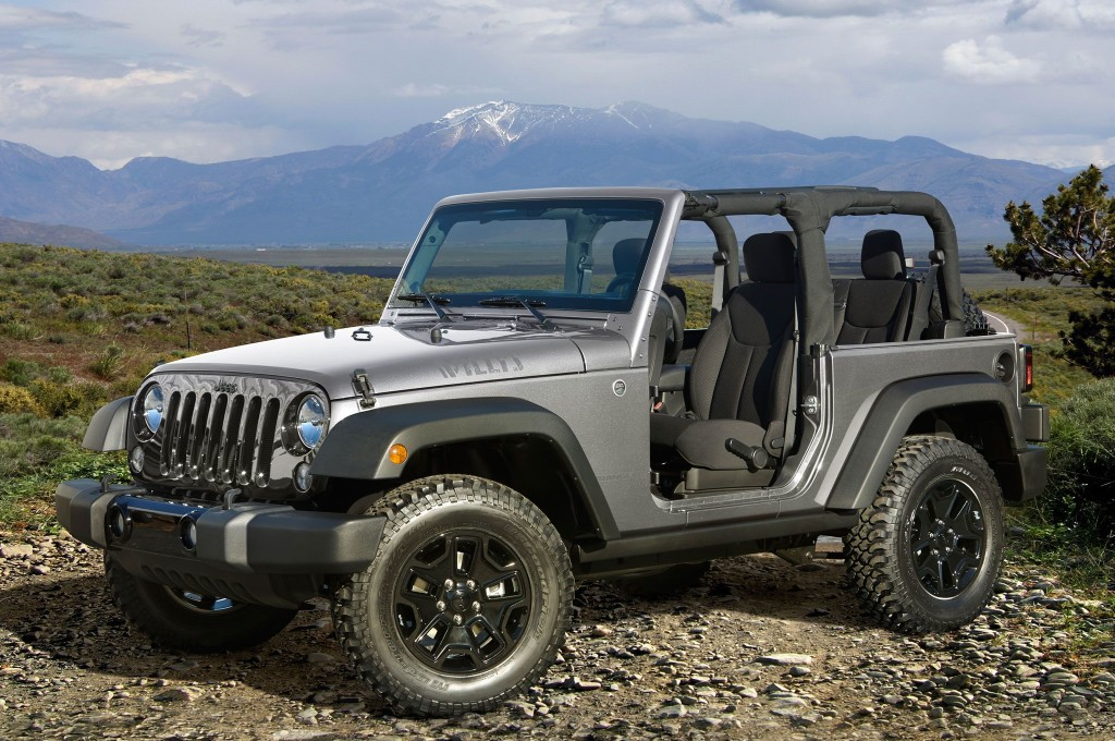 A silver 2016 Jeep Wrangler Willys with no doors or top is parked on a rocky hill with mountains in the distance.