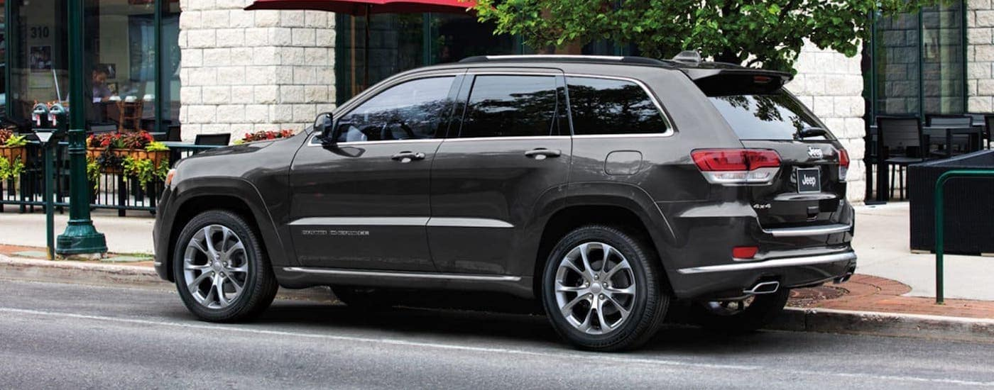 A dark gray 2019 Jeep Grand Cherokee is parked on a city street.