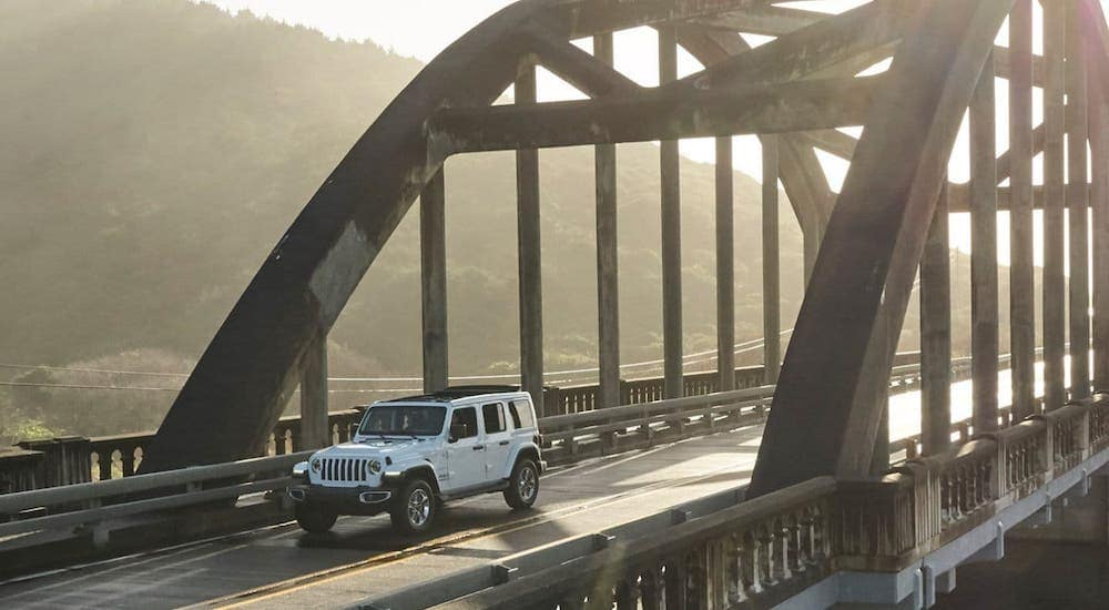 A white 2019 Jeep Wrangler Unlimited is driving over a bridge.