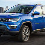 A blue 2017 Jeep Compass Longitude is driving with a city in the distance. Check one out at a Jeep dealer in Colorado.