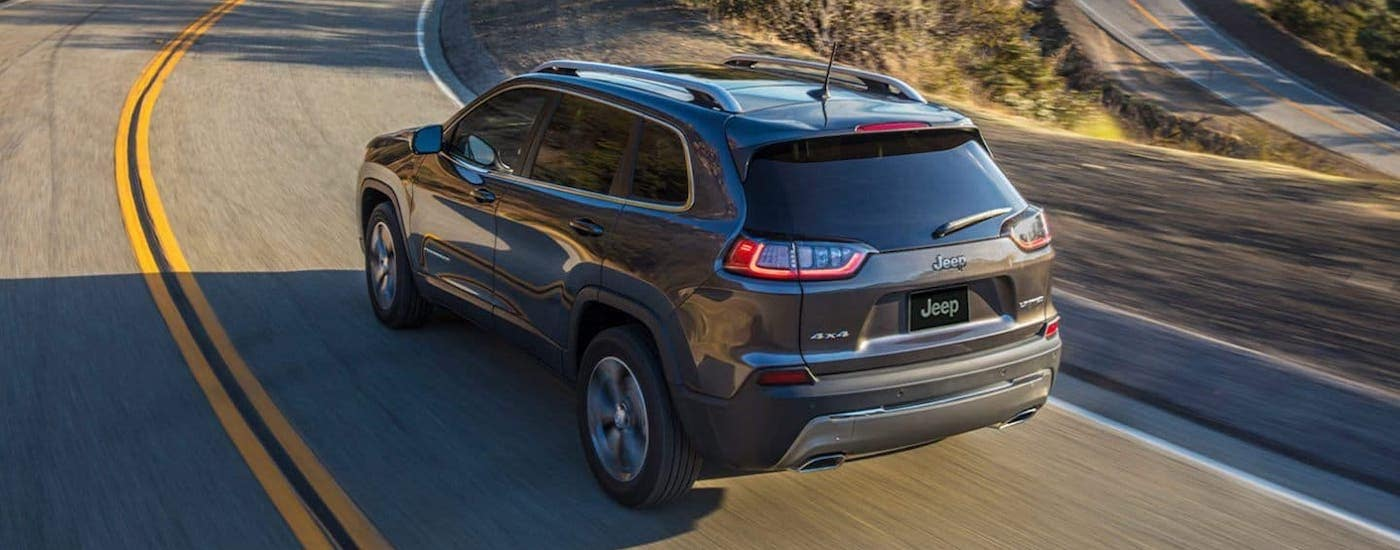 A gray 2020 Jeep Cherokee is driving on a mountain highway, find one at your local Jeep dealers in Colorado.