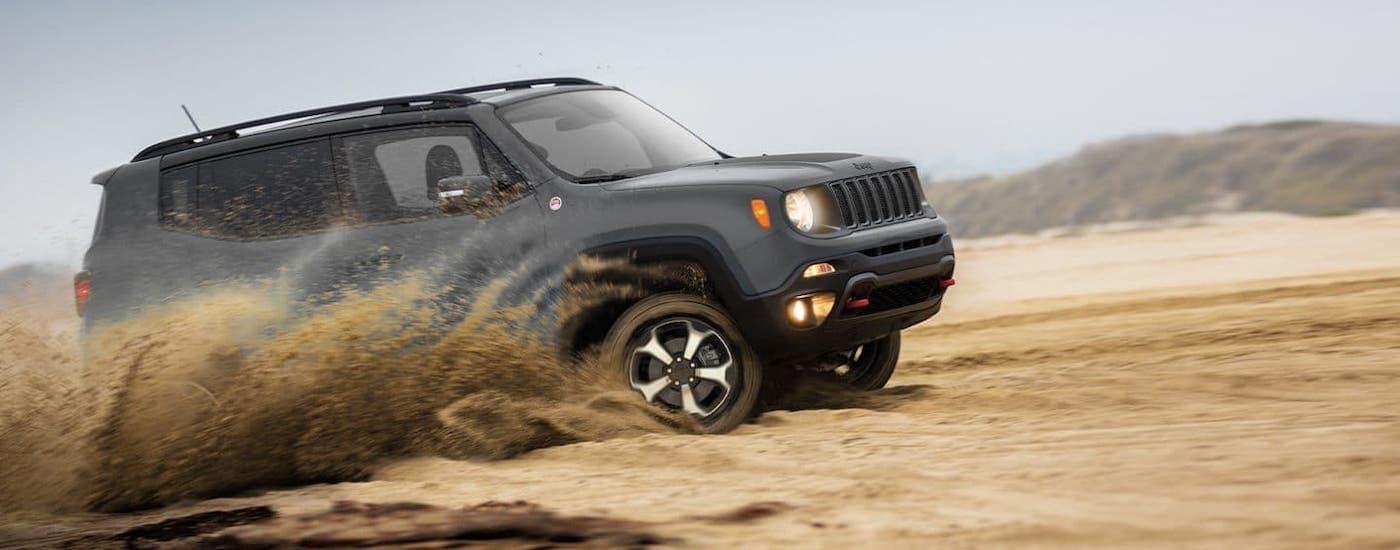 A dark gray 2020 Jeep Renegade is kicking up sand near Colorado Springs, CO.