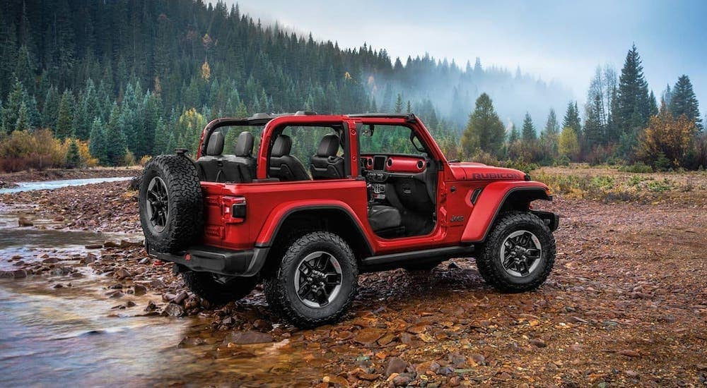 A red 2020 Jeep Wrangler, with no top or doors, is crossing a stream in the wilderness.