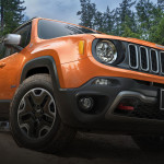 An orange 2015 Jeep Renegade is shown from a low angle on a woodland trail. Check one out today at your local Jeep dealership in Colorado.