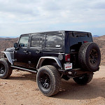 A black 2016 Jeep Wrangler Unlimited is parked atop a desert hill. Find an SUV like this at your Jeep dealers in Colorado.