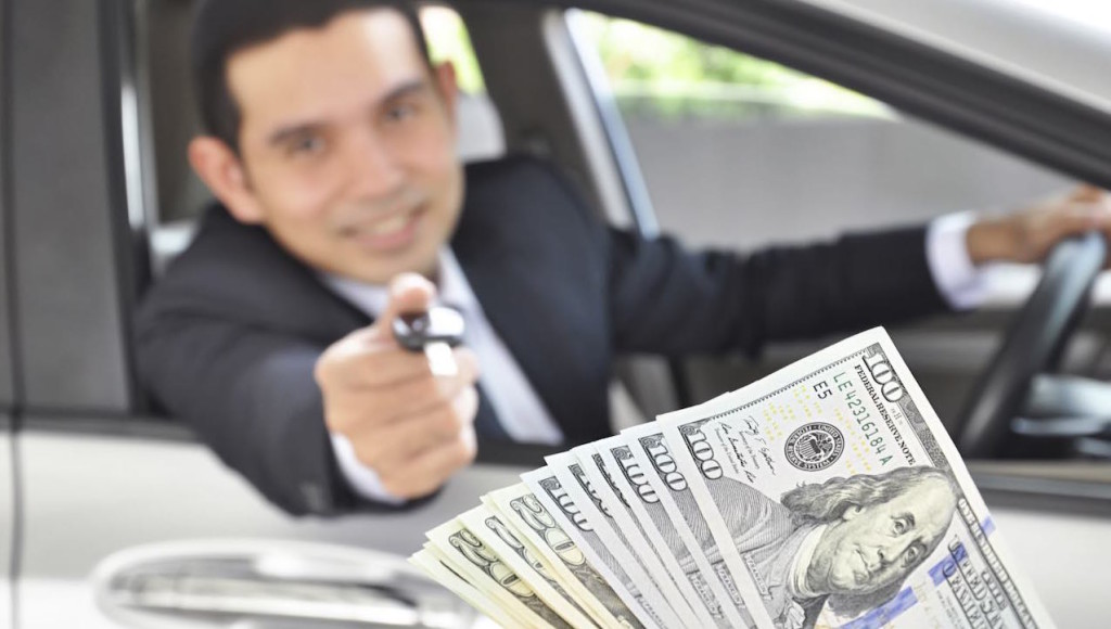 A man is leaning out a car window and holding a key in Colorado Springs while money is fanned out next to the camera.