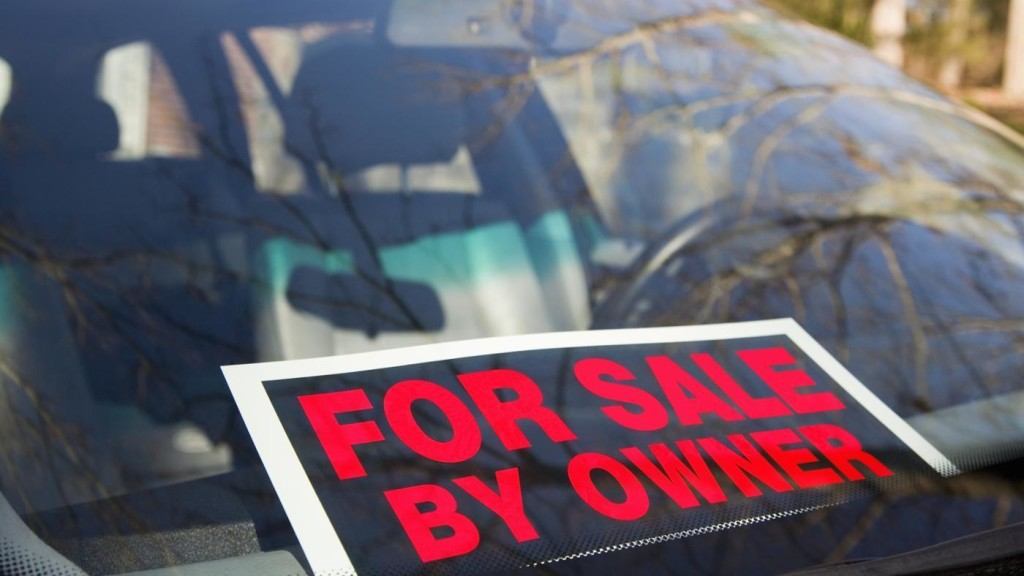 A For Sale By Owner sign is on the windshield of a car in Colorado Springs.