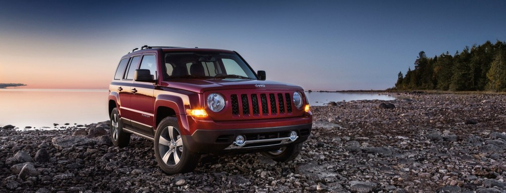 A red 2017 Jeep Patriot is parked on a rocky beach at sunset.