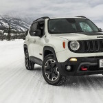 A white 2017 Jeep Renegade is driving on a snowy road.