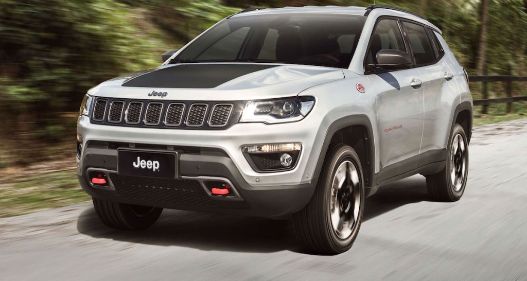 A silver 2017 Jeep Compass Trailhawk is driving on a woodland road.
