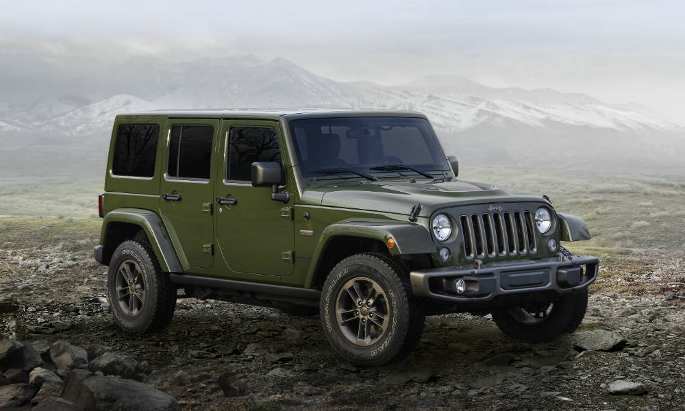 A green Jeep Wrangler Unlimited from Jeep dealers in Colorado is parked in front of misty mountains.