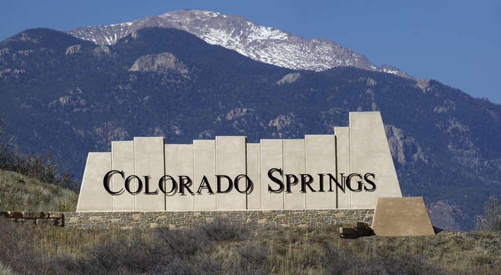 Stone Colorado Springs sign in front of tall mountains