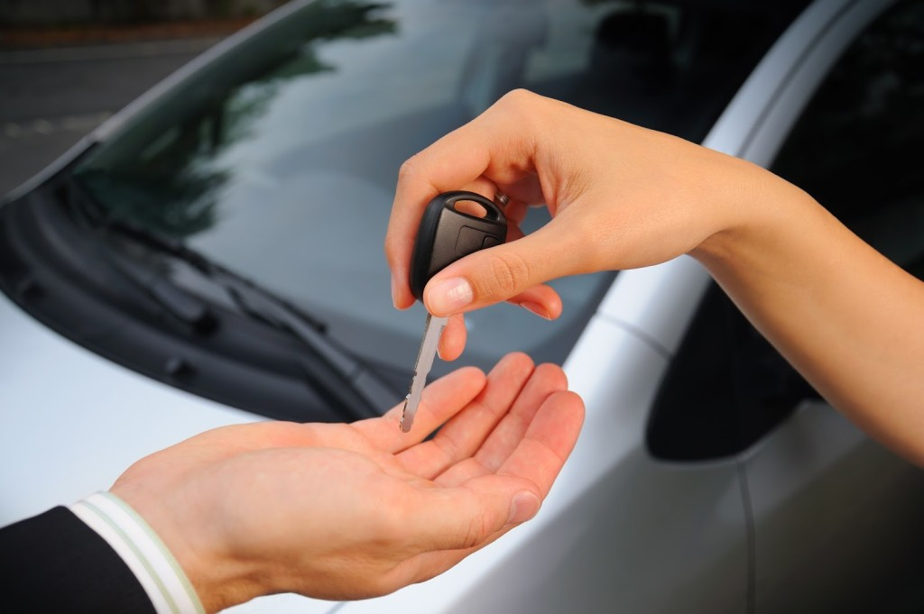 A woman is selling her car and handing keys to a salesman in front of a silver car.