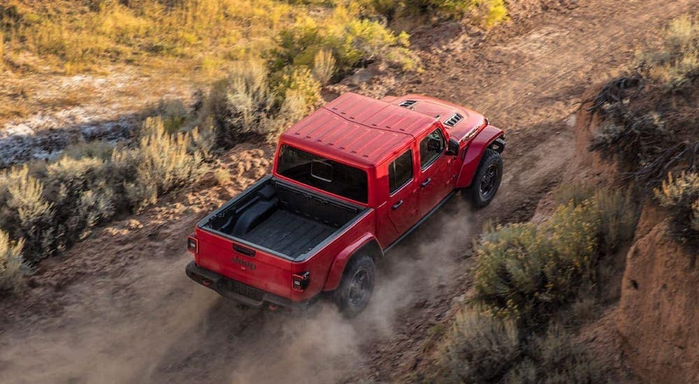 A red 2020 Jeep Gladiator is driving on a dirt road near Colorado Springs, shown from above.