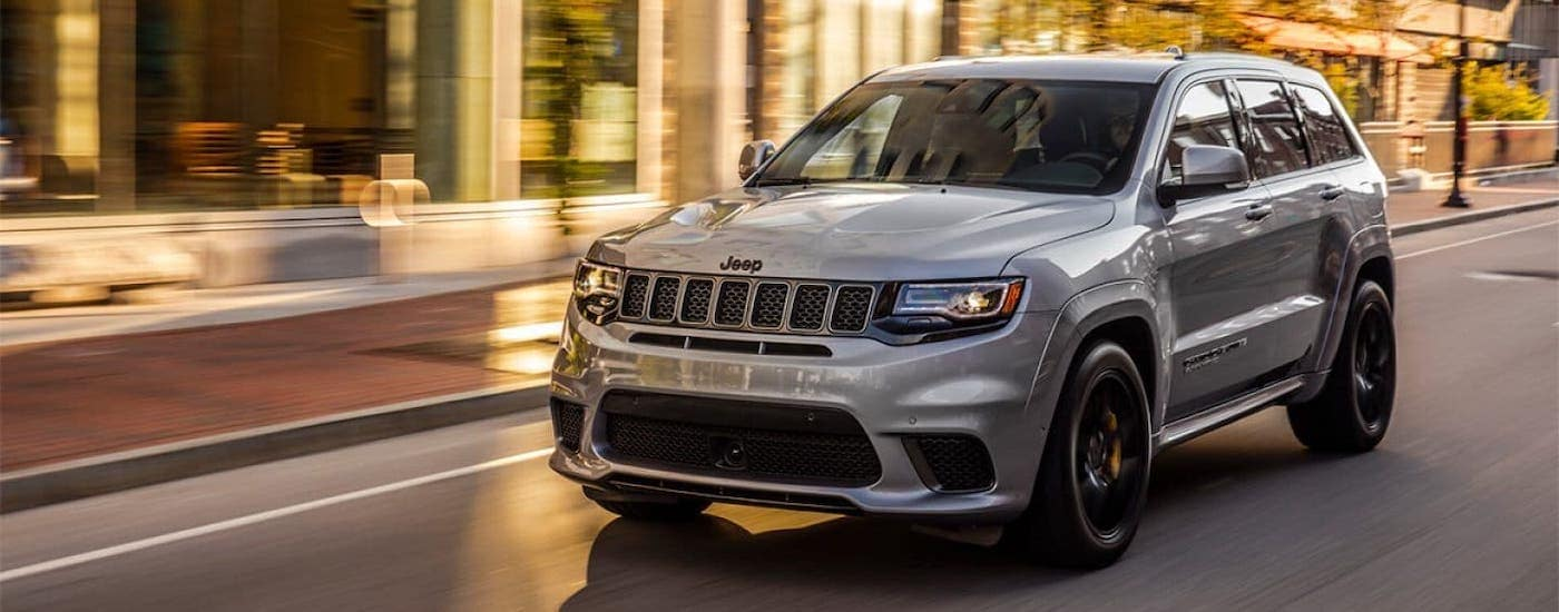 A silver 2020 Jeep Grand Cherokee is driving on a city street.