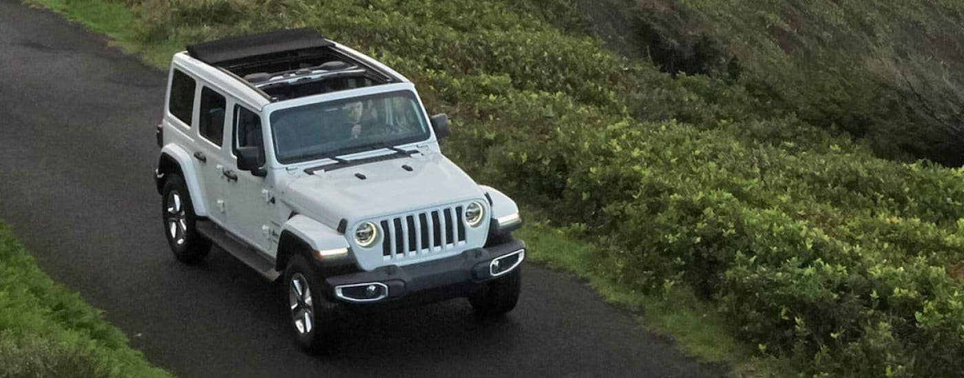 A popular Jeep lease in Colorado Springs, a white 2020 Jeep Wrangler Unlimited is driving on a rural road and shown from a high angle.