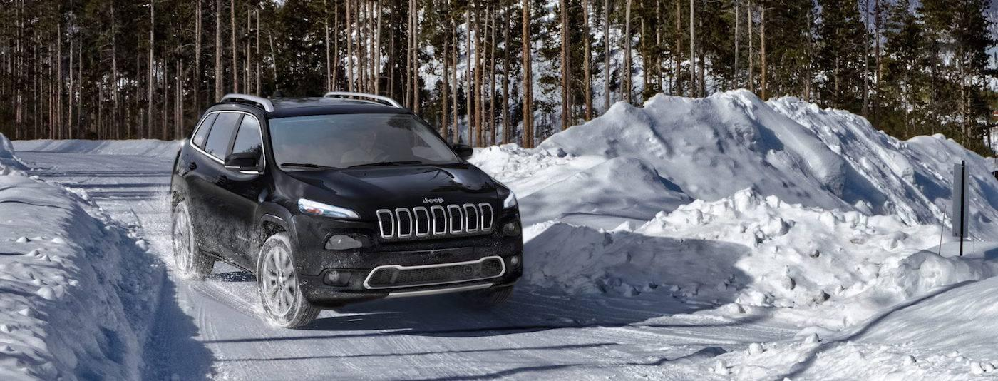 Black 2017 Jeep Cherokee Overland driving on a snowy trail in Colorado Springs CO.