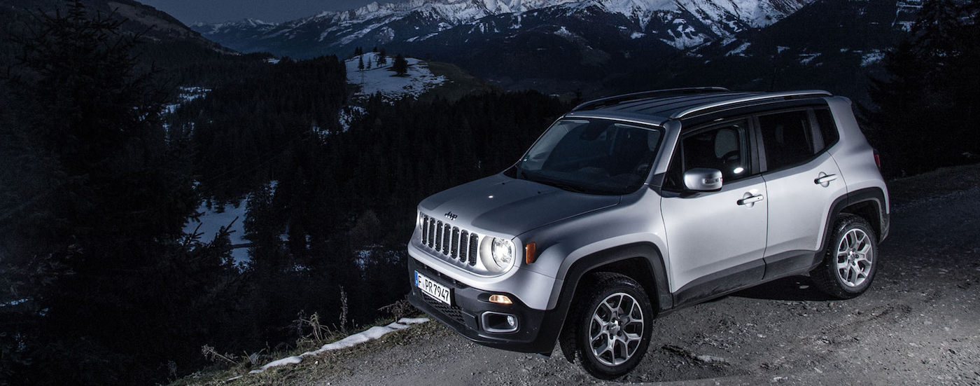 New Silver 2017 Jeep Renegade driving at night on the side of a snowy mountain road in Colorado Springs, CO.