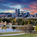 Green grass, trees, and a pond in front of tall Denver buildings, mountains, and an orange sky
