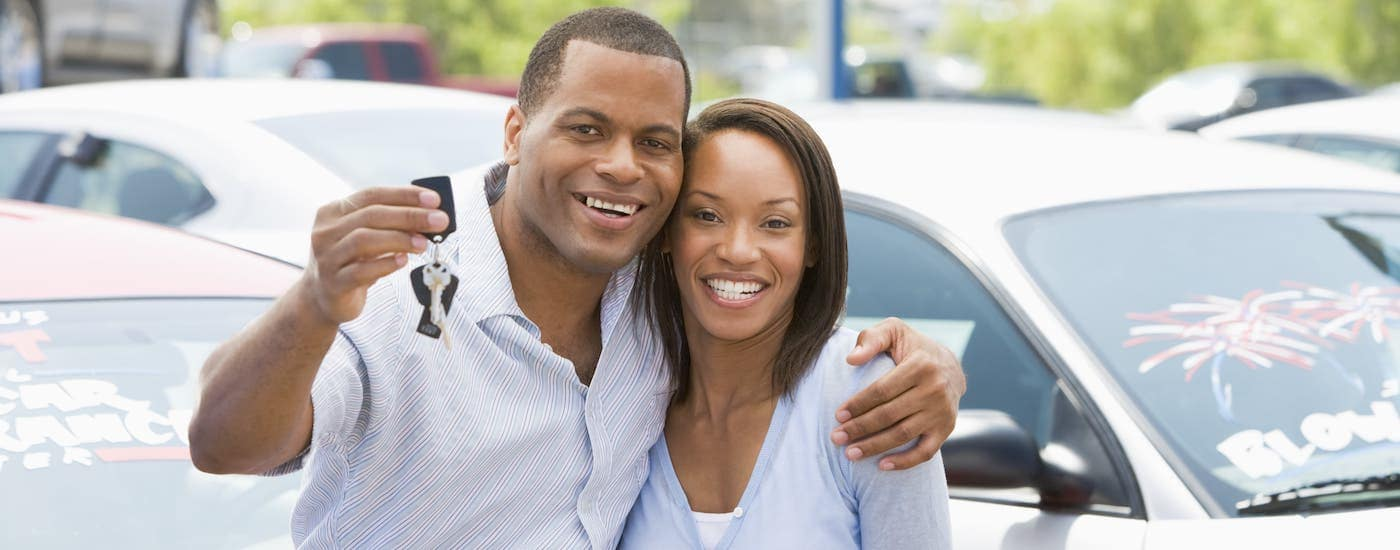 A couple is holding keys to their used car in front of a row of cars.