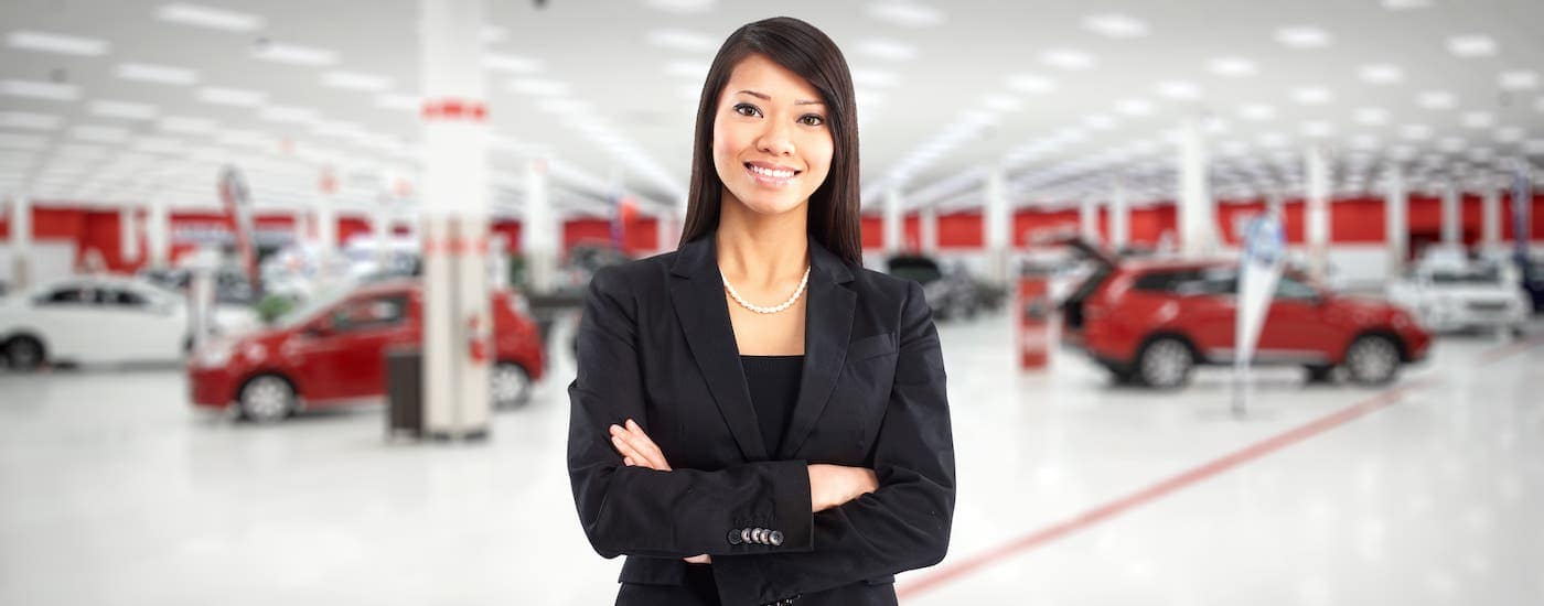 A saleswoman is standing in front of cars in a Colorado Springs showroom.