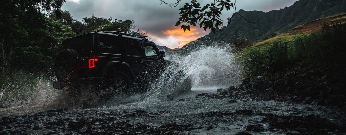 A black 2020 Jeep Wrangler Unlimited is crossing a river at dusk.