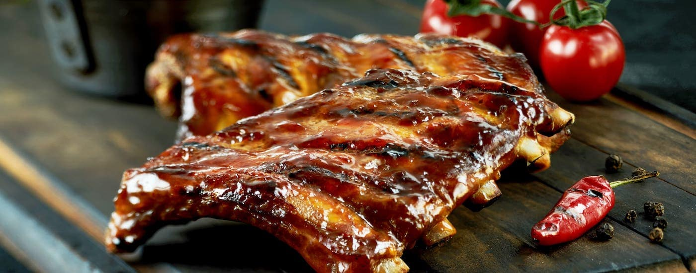 A rack of ribs is sitting on a wooden plank next to tomatoes and a pepper at a Colorado Springs BBQ restaurant.