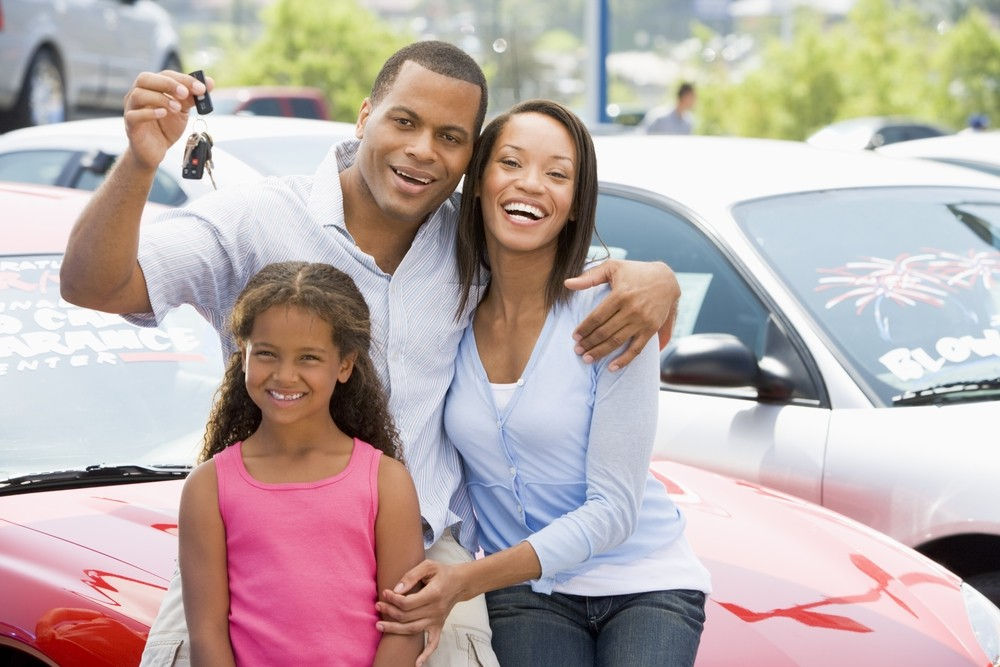 A family of three is holding up the keys to their new car and are sitting in a dealership lot.