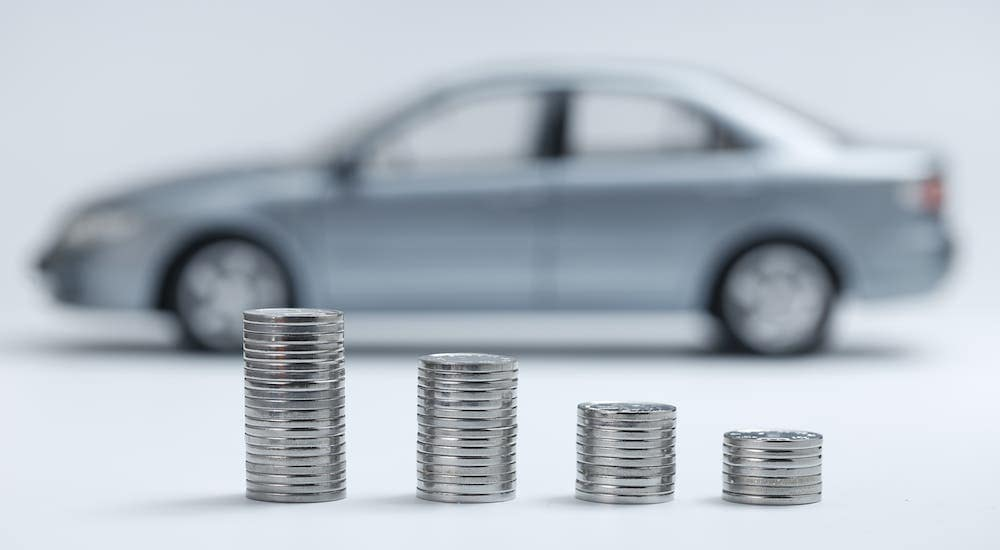 Stacks of nickels of different heights are in front of a distant and out of focus car.