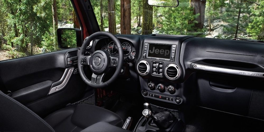 A popular Jeep for sale in Colorado Springs, a black interior dashboard and front seat are shown in a 2017 Jeep Wrangler.