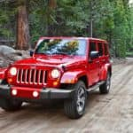 A red 2018 Jeep Wrangler Unlimited is driving on a woodland trail.