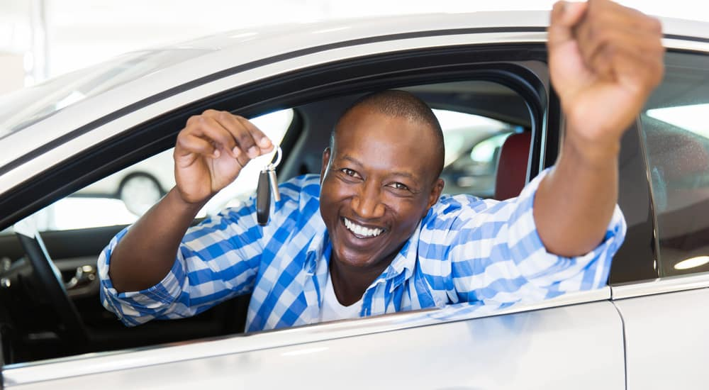Man in a blue and white plaid shirt sticking his head and arms out the window of a white vehicle, holding out car keys, and smiling
