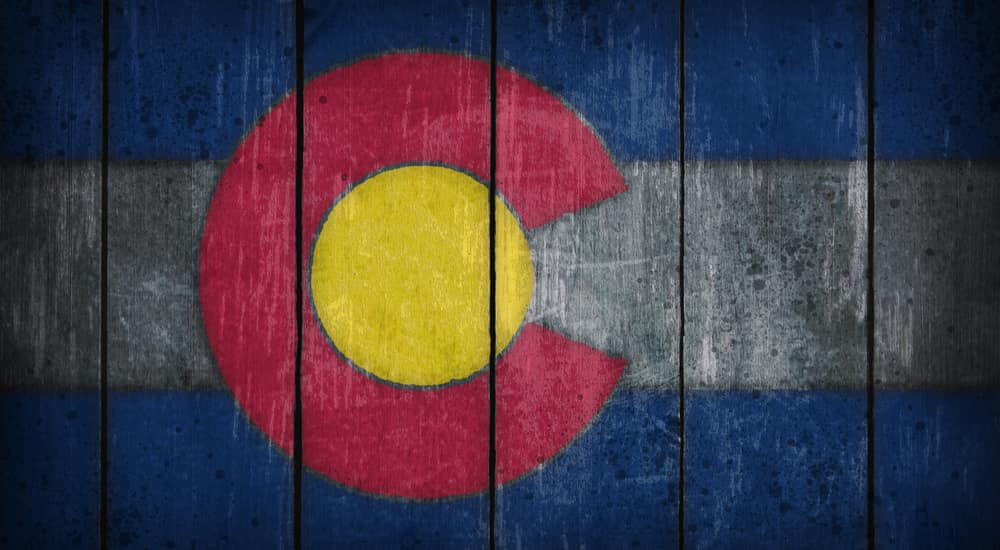 The Colorado flag is shown painted on wooden boards.
