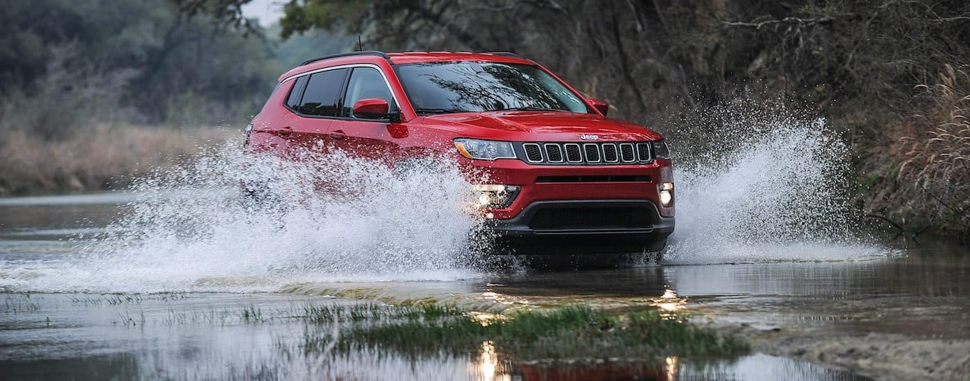Red 2018 Jeep Compass offroading in shallow water causing a splash
