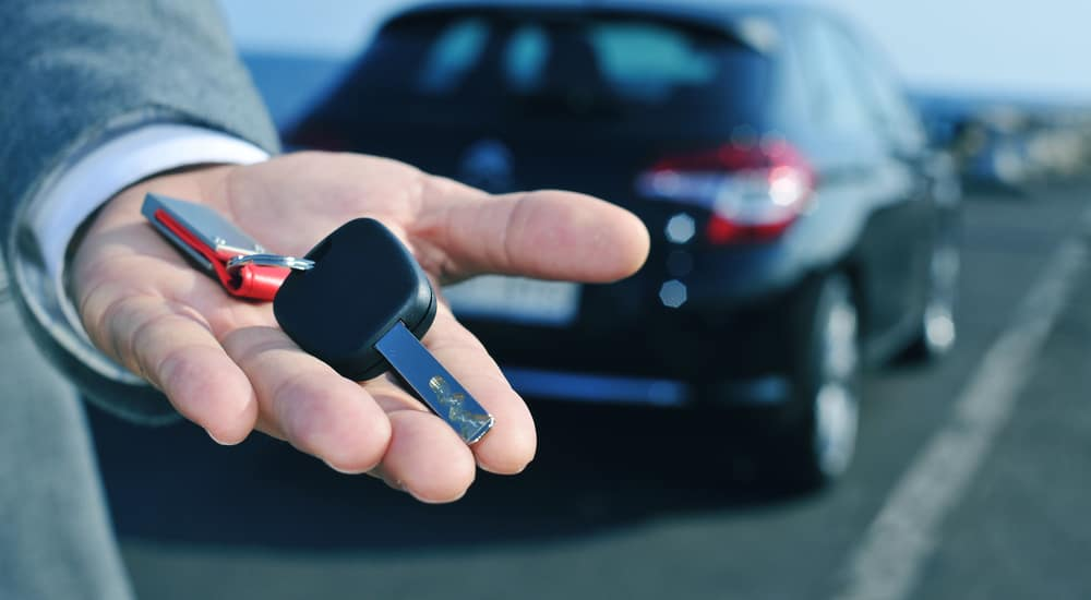 A hand is holding keys to used cars in Colorado Springs, CO.