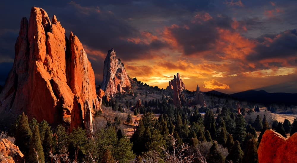 Tall orange rock mountains surrounded by trees in front of an orange, cloudy sky
