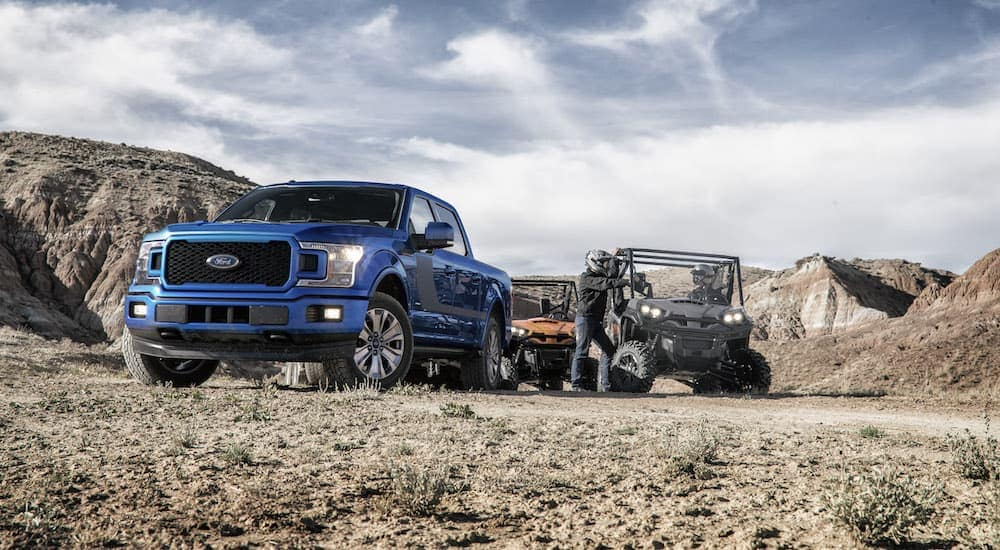 A blue 2018 Ford F-150, popular among used cars in Colorado, is off-road with side-by-sides.